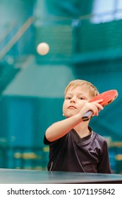 boy athlete plays flying table tennis ball in the tennis hall