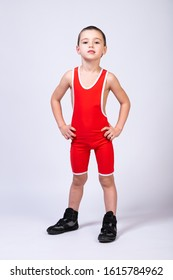 A boy athlete in sportswear and wrestling outfits is standing straight with his hands on his sides and looking at the camera on a white isolated background.  The concept of a little fighter athlete.