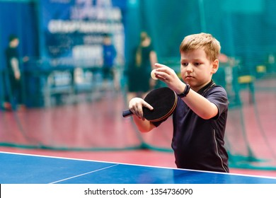 boy athlete throws the ball in table tennis. black fitness bracelet on baby's hand