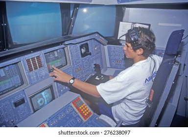 A boy attending space camp at the George C. Marshall Space Flight Center in Huntsville, Alabama, sits in the cockpit of a space shuttle flight simulator