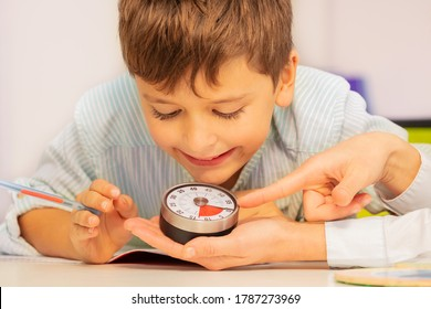 Boy with autism spectrum disorder during ABA therapy look at lesson timer in teachers hands understanding time concept