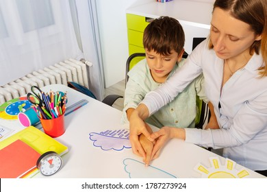 Boy with autism spectrum disorder learn weather using cards, teacher hold hands and point to correct one view from above