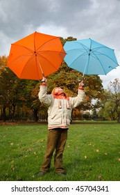 Boy in autumn park. Holds over head two color umbrellas under cloudy sky.