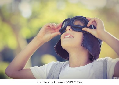 Boy in aviator goggles looking up in park