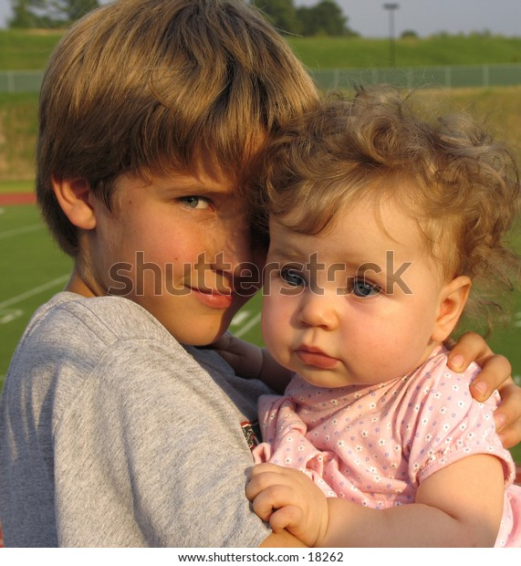 boy with baby sister in an outdoor setting