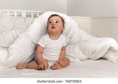 boy baby t-shirt lies under a blanket in a big white bed