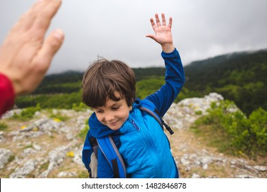 A boy with a backpack climbed to the top of the mountain and gives five. Traveling with children. The child holds out his hand to dad. Kid on the background of cloudy sky. Active lifestyle.