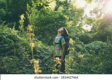 Ein Junge mit Rucksack geht durch den Wald, ein Kind erforscht Tierwelt, ein Kind steht allein unter den Bäumen, ein Portrait eines Jungen.