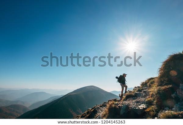 Boy backpacker traveler walk up on mountain top in contrast sun light