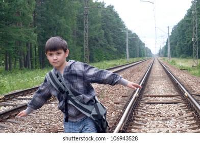 The boy balances on tracks