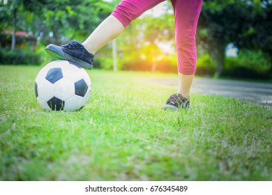 Boy with ball on green grass with sunshine background.