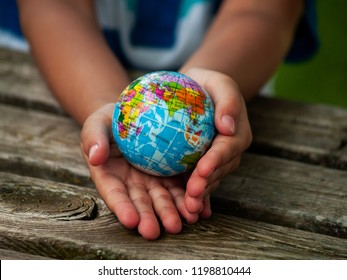 A boy with a ball of the world or planet Earth in his hands. Ecology concept
