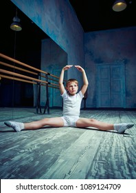 boy ballet dancer doing exercise at  dance class near the barre indoors
