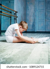 boy ballet dancer doing exercise and stretching at  dance class near the barre indoors