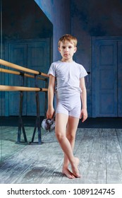 boy ballet dancer posing with pointes in his hands at  dance class near the barre indoors