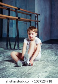 boy ballet dancer putting on pointes at  dance class near the barre indoors