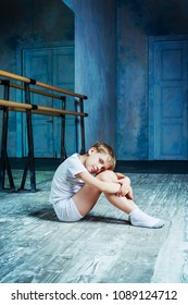 boy ballet dancer sitting on the floor and resting at  dance class near the barre indoors