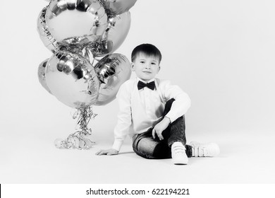 Boy  with balloons is sitting in Studio on white background