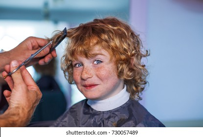 boy in the barbershop, happy boy with freckles smiling hairdresser, barber and kid