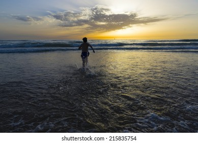 boy bathing on the beach at dusk on a beach in Andalusia, Spain