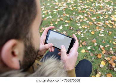 Boy with a beard looking at a smartphone in the woods