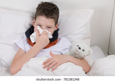 the boy is in bed, his throat hurts, he blows his nose into a paper disposable handkerchief
