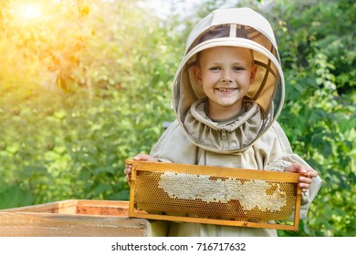 The boy beekeeper holds in his hands a honeycomb with fresh honey.