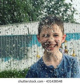 A boy behind the window covered with rain drops