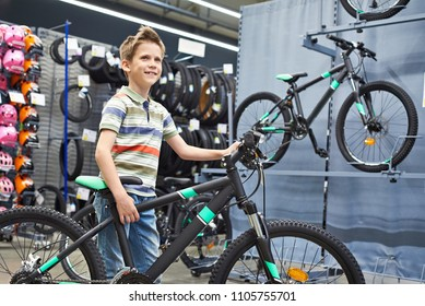 Boy and bicycle in a sports shop