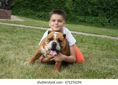 Boy and big bulldog sit on the grass