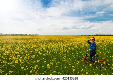 Boy with bike on country field with flowers in sunny day in spring