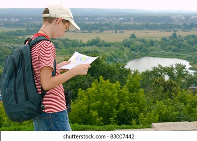 Boy with binoculars, backpack and map on a hike