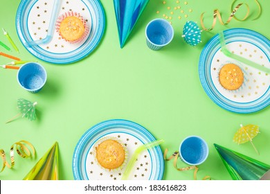Boy birthday green table setting from above with muffins, drinks and party gadgets. Background layout with free text space.