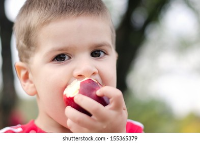 Boy bitten by a juicy red apple