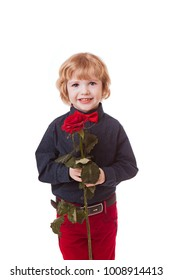 boy in a black shirt, red pants and a red bow tie on a white background holds in his hands and sniffs a red rose