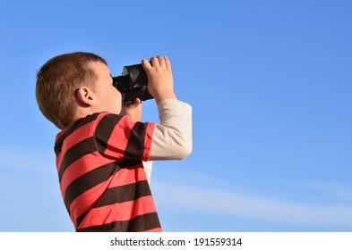 Boy in black-red t-shirt exploring the clear blue sky through binoculars.