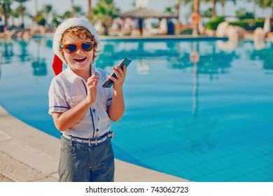 a boy with blond hair and freckles in a Santa Claus hat holding a cell phone in hand on the background of a pool of water, smartphone and kid