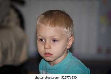 a boy with blond hair plays at home