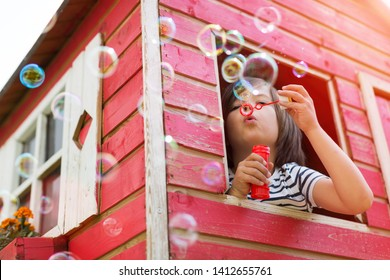 Boy blowing bubbles from a wooden playhouse