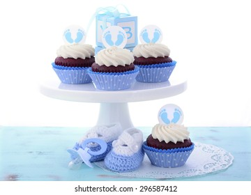 Its a Boy Blue Baby Shower Cupcakes with baby feet toppers and decorations on shabby chic blue wood table.