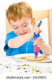 Boy in blue decorating biscuits with pink icing and sweets