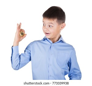 Boy in blue shirt looks with surprise at the bitcoin in his hand. Isolated on white background. The concept of developing a new generation of virtual currency.
