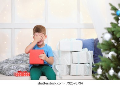 Boy in a blue t-shirt opens a box with a Christmas present sitting on a window sill next to a Christmas tree