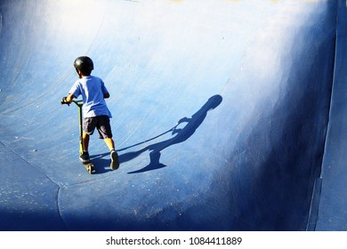 Boy with a blue t-shirt riding a scooter in a blue painted ramp in the skatepark