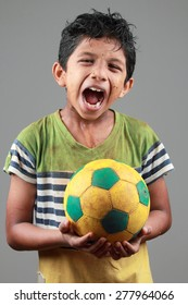 Boy with body smeared with mud holds a football and shows energy