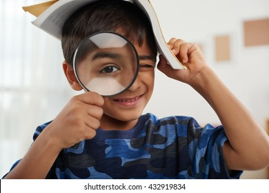 Boy with a book looking through magnifying glass