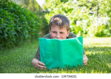 boy with a book on the grass on a sunny day
