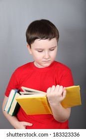 Boy with  books on a gray background.