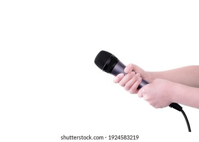 Boy both hands holding dynamic microphone up isolated on a white background. Kids sing, speak, talk, interview, present, karaoke, hosting, technology and education background. Close up and copy space.