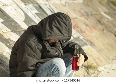 Boy with a bottle of hands sit under a bridge